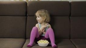 Menina que senta-se no sof? e que come sopros do milho Puffcorns do sorriso e do gosto da crian?a vídeos de arquivo