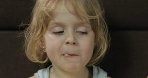 Menina que senta-se no sof? e que come sopros do milho Puffcorns do sorriso e do gosto da crian?a video estoque