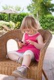 Menina que senta-se no telefone celular de observação da cadeira de vime Imagem de Stock Royalty Free