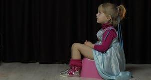 Menina que senta-se no urinol e na tevê de observação video estoque