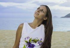 Menina que senta-se no vestido na praia Por do sol Sea Foto de Stock