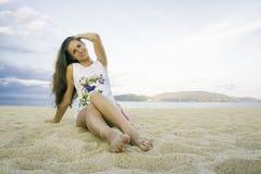 Menina que senta-se no vestido na praia Por do sol Sea Imagens de Stock