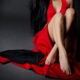 Menina que senta-se no vestido vermelho Foto de Stock Royalty Free