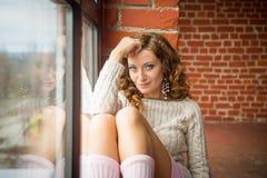 Menina que senta-se no windowsill Vista superior imagens de stock