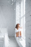 Menina que senta-se no windowsill Vista superior imagens de stock royalty free