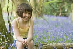 Menina que senta-se nos bluebells Fotografia de Stock Royalty Free