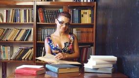 A menina que senta-se nos livros de leitura da biblioteca está preparando-se para exames video estoque