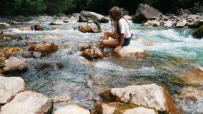 A menina que senta-se nos rios de pedra da montanha, mão condu-los através da água que apreciam o frescor filme