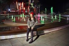 Menina que senta-se pela fonte na noite imagem de stock
