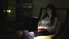 Menina que senta-se pela janela com um portátil na noite filme