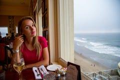 Menina que senta-se pela janela com uma vista para o mar fotos de stock royalty free