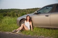Menina que senta-se pelo carro Imagem de Stock