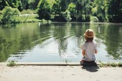 Menina que senta-se pelo lago foto de stock royalty free