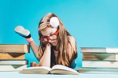 Menina que senta-se pelos livros, estudando imagem de stock