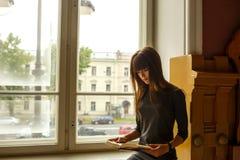Menina que senta-se perto da janela que lê um livro foto de stock royalty free