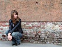 Menina que senta-se perto da parede do grunge Imagem de Stock