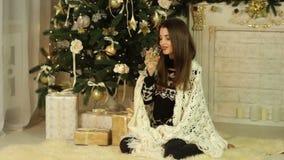 Menina que senta-se perto de uma árvore de Natal e que guarda um vidro do champanhe vídeos de arquivo