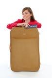 Menina que senta-se perto de uma mala de viagem foto de stock royalty free