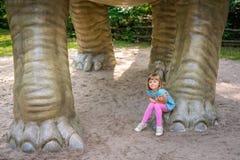 Menina que senta-se sob a escultura enorme do dinossauro do Diplodocus imagens de stock