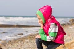 A menina que sentam-se na praia rochosa e o mar dirigem em sua mão que olha ao quadro Fotografia de Stock Royalty Free