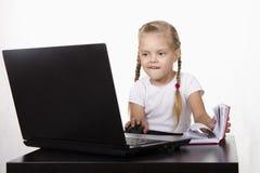 A menina que sentam-se na tabela, trabalhando em um portátil, e registros em um caderno Fotografia de Stock