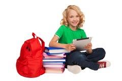 Menina que sentam-se no assoalho perto dos livros e saco que guarda a tabuleta Imagens de Stock Royalty Free