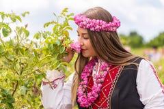 Menina que sente o aroma de rosas cor-de-rosa búlgaras em um jardim fotografia de stock royalty free