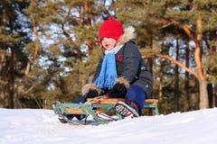 Menina que sledding no dia de inverno ensolarado Fotografia de Stock Royalty Free