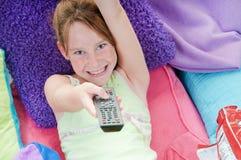 Menina que snacking na cama que presta atenção à tevê foto de stock
