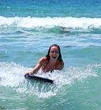 Menina que sorri ao montar uma onda azul grande em uma placa do corpo no mar azul em um dia ensolarado. fotografia de stock royalty free