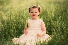 Menina que sorri, criança que senta-se na grama Fotografia de Stock Royalty Free