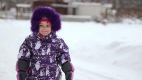 Menina que sorri olhando a câmera no inverno na rua video estoque