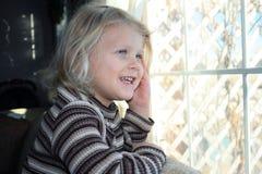 Menina que sorri pelo indicador. Imagens de Stock Royalty Free