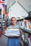 Menina que sorri quando levar registrar na biblioteca imagens de stock royalty free