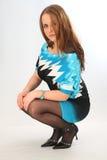 Menina que squatting com metade da face Imagem de Stock Royalty Free