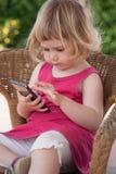 Menina que surfa com o dedo no telefone celular Fotos de Stock