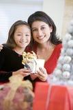 Menina que surpreende sua matriz com presente do Natal Imagens de Stock