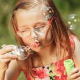Menina que tem bolhas de sabão de sopro do divertimento no parque Fotografia de Stock