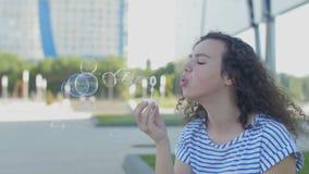 Menina que tem bolhas de sopro do divertimento video estoque