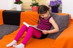 Menina que tem a leitura do divertimento imagens de stock royalty free
