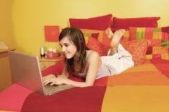 Menina que tem a mensagem no portátil Fotografia de Stock Royalty Free