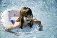 Menina que tem a natação do divertimento na associação fotografia de stock