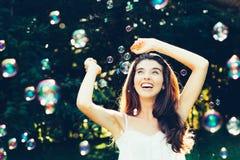 Menina que tem o divertimento com bolhas Foto de Stock Royalty Free
