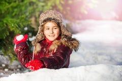 Menina que tem o divertimento com o inverno da luta da bola de neve exterior Fotografia de Stock Royalty Free