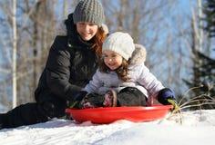 Menina que tem o divertimento com sua mãe durante o inverno fotografia de stock royalty free