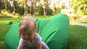 Menina que tem o divertimento em beanbags na natureza vídeos de arquivo