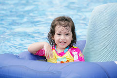 Menina que tem o divertimento em um flutuador azul Fotos de Stock Royalty Free