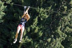 Menina que tem o divertimento em uma aventura do parque da corda Fotos de Stock