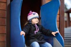 Menina que tem o divertimento na corrediça exterior de playground/on imagem de stock royalty free