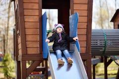 Menina que tem o divertimento na corrediça exterior de playground/on fotografia de stock royalty free